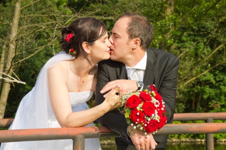 newly wed couple with wedding gown, dark suit and rose bridal bouquet: groom and bride kissing affectionately photo