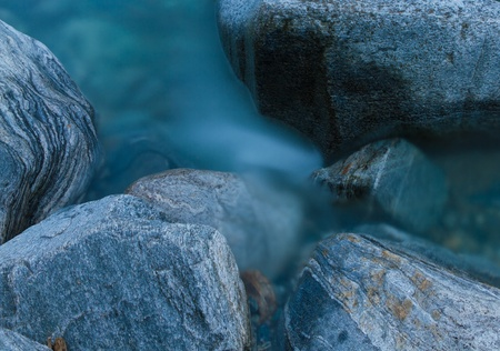mountain river splashing over stones and rocks at sunset, silky water from long exposure photo