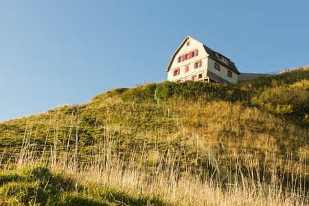 refuge: classic wood planked mountain guesthouse in early morning light, Switzerland