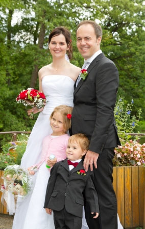 newly wed couple and children with wedding gown, dark suit and rose bridal bouquet: outdoors in park happy Stock Photo - 13688495