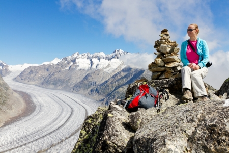 aletsch: concept for hiking, climbing, walkig and outdoor adventures: woman on mountain top with backpack and sticks above Aletsch glacier Switzerland Stock Photo