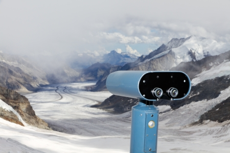 swiss alps: concept for for look out, observation and forecast:  binoculars view over panorama view above Aletsch glacier starting to disappear in clouds, Switzerland