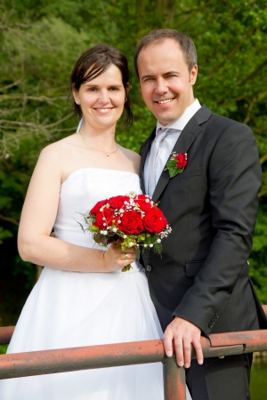 wed: newly wed couple with wedding gown, dark suit and rose bridal bouquet: groom and bride hand in hand proud and happy