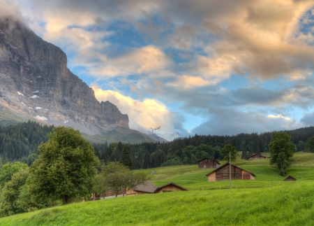 Mountain huts in valley at sunset in front of mountain Eiger north face, Switzerland
