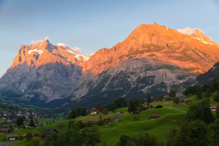 alpenglow: Alpenglow over alpine town Grindelwald in valley at sunset in front on mountain Eiger north face, Switzerland