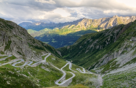 Old road with tight serpentines on the southern side of the St. Gotthard pass bridging swiss alps at sunset in Switzerland, europe Stock Photo - 16851925