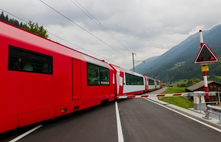 Glacier express train crosses road with closed railway crossing gate, Switzerland photo