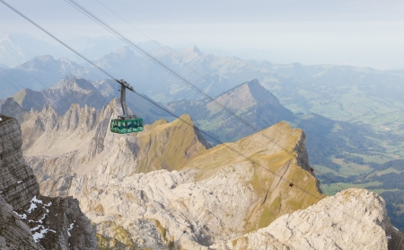 cable car going up mountain Saentis over ragged tops of Churfirsten, Switzerland photo