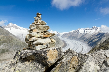 concept for hiking, climbing, walkig and outdoor adventures   mountain top with rock cairn marking above Aletsch glacier Switzerland photo
