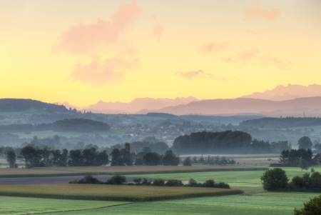 farmland with fog, mist and hills at sunrise, Switzerland photo