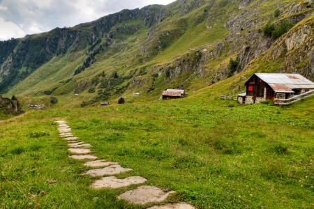 valais: hiking path leading along alpine valley with wooden huts, Switzerland Stock Photo