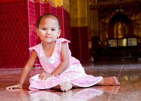 young burrmese girl dressed up nicely for temple visit with make up called thanaka ear rings, neclace and pink dress, Burma photo