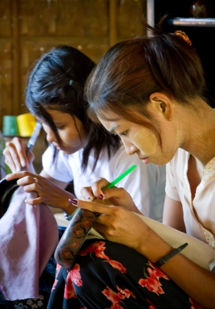2 november: NYAUNG U, BURMA-NOV.  2: Unidentified women produce lacquerware dishes on November 2, 2011 in Nyaung U, Burma.
