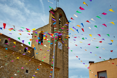 Begur, Costa Brava, Catalonia, Spain: Church of Sant Esteve dEsclany? with colored flags. Stock Photo