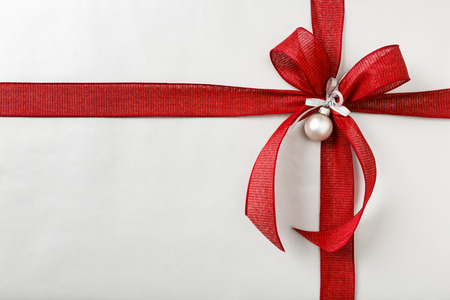 Beautiful, festive, fancy Christmas gift present with silver wrapping paper and bright red wired fabric ribbon bow. Horizontal background border with empty blank space.