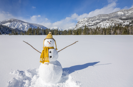 Cute fun funny snowman snow person with knit hat and scarf in snowy winter landscape field with mountains and blue sky
