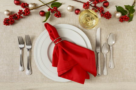 Beautiful, festive Christmas dinner party table setting place setting with white ceramic plates, silverware, red cloth napkin and white wine in wineglass. Home entertaining elegant fine dining holiday decorations. Stok Fotoğraf