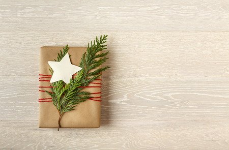 Christmas gift present wrapped in sustainable recycled brown kraft wrapping paper with natural botanical evergreen decorations and a blank, star-shaped gift tag on rustic whitewashed  light wood background. Simple, modern, country style holiday decorations. Stock Photo