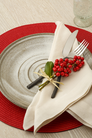 Festive Christmas dinner table setting place setting with rustic silverware, handmade pottery plate, linen cloth napkin and natural botanical holly decorations. Holiday parties home entertaining.