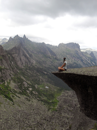 A lonely young woman sits on the edge of a cliff.