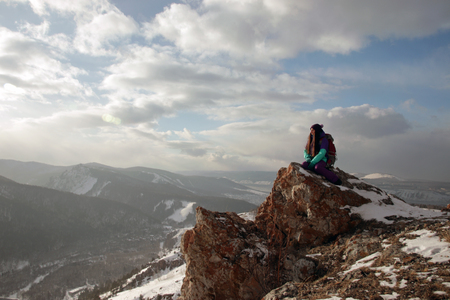 A lonely young woman sits on the edge of a cliff and enjoys the scenery of the mountains. Banco de Imagens