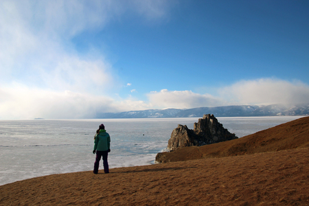 A young woman stands on the shore of the frozen lake Baikal. Banco de Imagens
