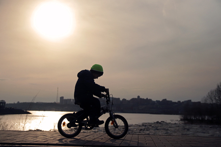 Silhouette of a boy riding a Bicycle in the Park. HD