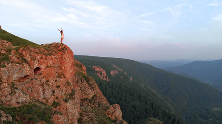 Young happy woman standing on the edge of a cliff. Banco de Imagens