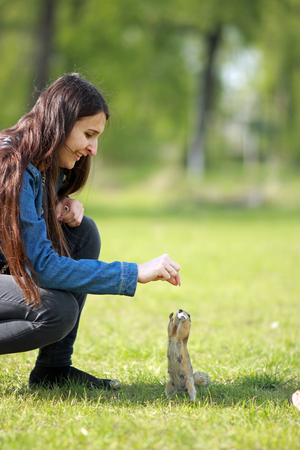 Young attractive woman feeding a hungry gopher bread. Banco de Imagens