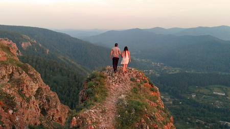 A man and a woman stand on top of the mountain at sunset.