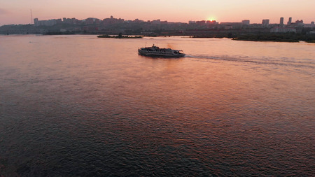 Aerial view of the ship sailing on the river in the city at sunset.