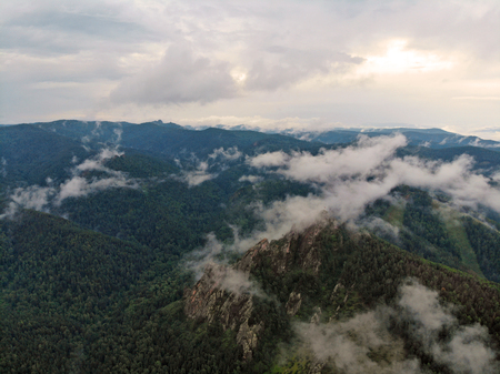 Aerial viw of fog among the mountain peaks. Bad weather and fog in the Siberian nature reserve Stolby.