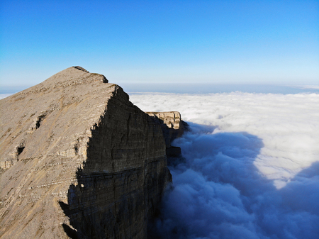 Mountain peaks of the Caucasus towering above the clouds. Fog in the mountain gorge.