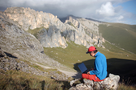 A man works on a laptop sitting on top of a mountain.