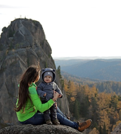 A young woman with her little son on top of a mountain.