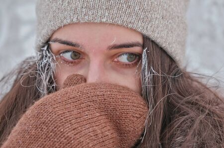 A young attractive woman hides her face from the cold.