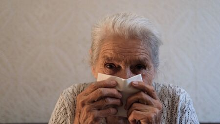 Portrait of an elderly woman sneezing. Archivio Fotografico