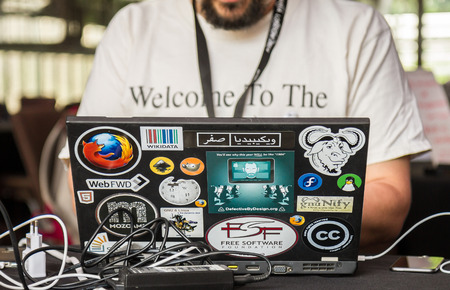 wikipedia: London, United Kingdom  August 9, 2014: A participant at the annual Wikimania conference for Wikipedians uses an old laptop.