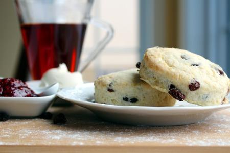 queso blanco: Las pasas scones con mermelada de frambuesas, queso blanco y una taza de t� Foto de archivo
