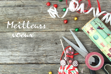 wooden board: Christmas concept. Material to wrap a gift on wooden board with the phrase Meilleurs voeux