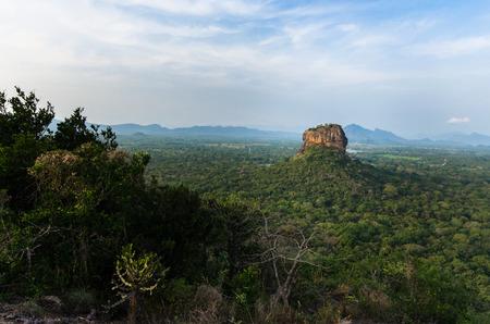 double page spread: Sigiriya Rock towering above the Sri Lanka landscape, seen from Pidurangala Rock, Sri Lanka.