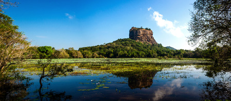 Panoramic picture of Sigiriya Rock Fortress, (a UNESCO world heritage Site) seen from Sigiriya Lake in the cultural triangle of Sri Lanka, Asia Stock Photo