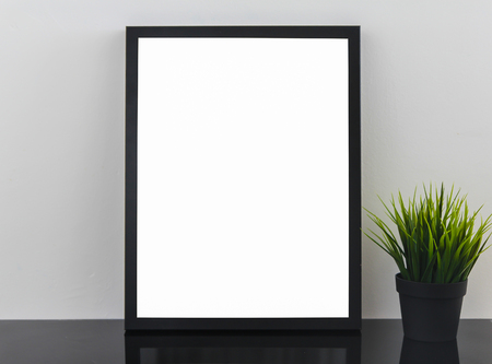 Empty Modern Black Frame On White Glossy Table With Decorative Grass In Flowerpot.Light Gray Background Wall