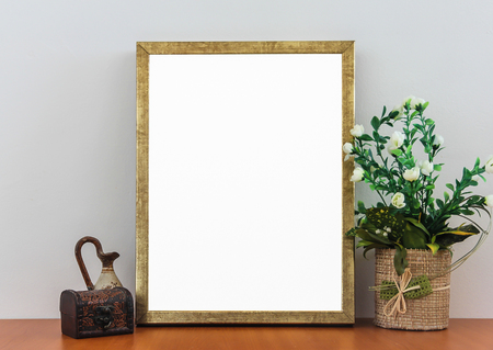 Empty Frame On Wooden Shelf With Decorative Flowers,Vintage Box and Antique Vase Gray Background Wall