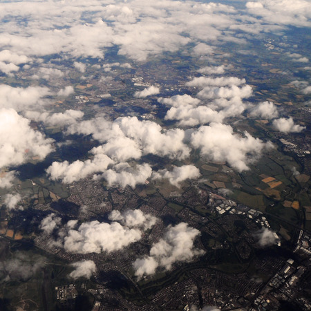 Fluffy clouds over land photo