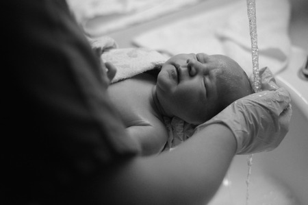 neonate: Gloved hand of a woman washing the head of a newborn baby under running water, black and white portrait Stock Photo
