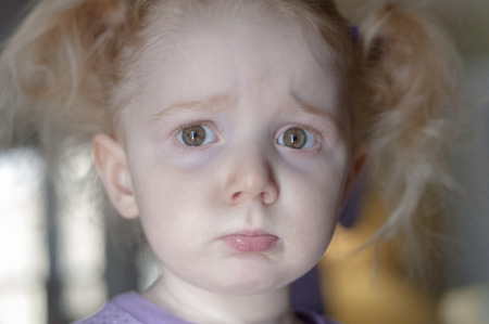 grieved: Close up portrait of a cute little redhead girl with a sad pouting expression and big sulky eyes looking straignt at the camera Stock Photo