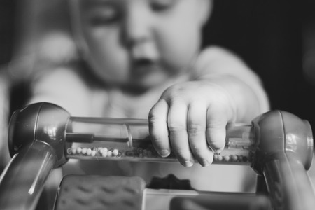 unknown gender: Black and white close up of baby playing with toy with focus on hand and toy in foreground