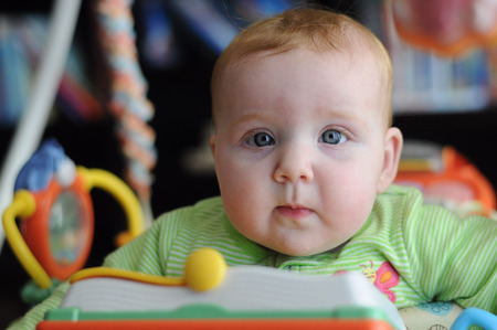unknown gender: Close-up portrait of cute baby in play gym toy looking at viewer Stock Photo