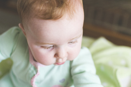 Close-up of cute baby looking down in crib with soft light